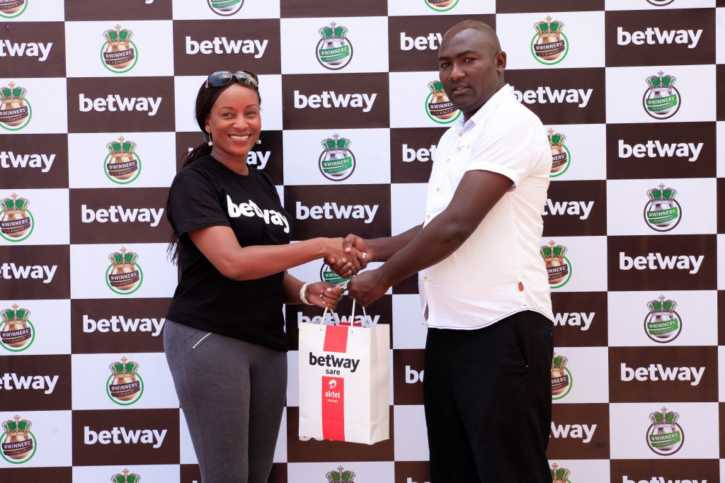 David Gikunda Kuura poses with a representative from Betway Kenya. Photo / COURTESY