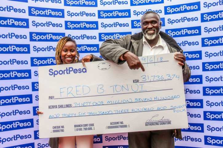 SportPesa Mega Jackpot winner Tonui receives his cheque from Jane Njoroge of SportPesa