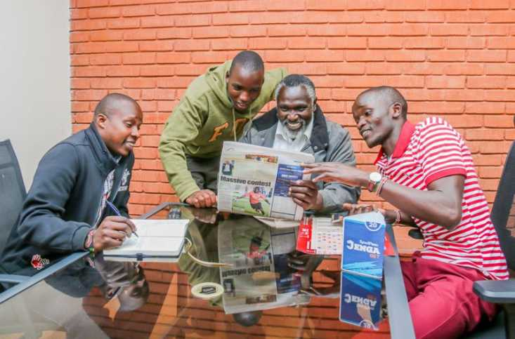 SportPesa Mega Jackpot winner Tonui examines the listings and odds on games in the newspaper. Photo / COURTESY