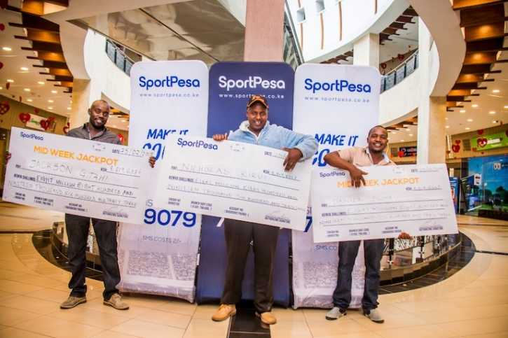 MILLIONAIRE'S PLAYGROUND: SportPesa Mid Week Jackpot winners (L to R) Jackson Gitahi, Nicholas Kirui and Daniel Sumaili pose with their cheques after receiving KSh8,819,633 each on Monday, February 25, 2018. PHOTO/SPN