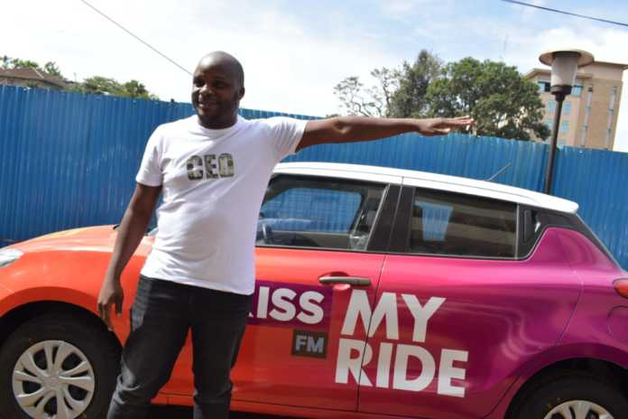 Kiss 100 presenter Jalang'o showcasing the brand new car that's up for grabs for free, courtesy of Kiss 100 Kenya